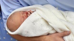 O recém-nascido George Alexander Louis nos braços do princípe William, ao sair da maternidade na terça-feira, dia 22 de julho.
