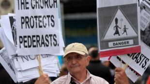 愛爾蘭示威者手舉牌子抗議教會包庇性侵犯者