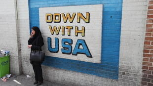 A woman standing next to an anti-US slogan painted at the former American embassy in the Iranian capital, Tehran.