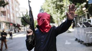 Militante armado nas ruas de Istambul, durante o funeral de uma das vítimas do atentado de Suruc.