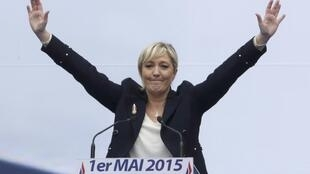France's far-right National Front political party leader Marine Le Pen waves during her May Day speech in front of the Paris Opera