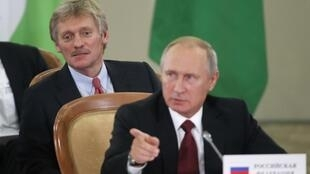 Дмитрий Песков (слева) и Владимир Путин на саммите СНГ в Сочи. Октябрь 2017