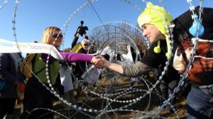 Slovènes et Croates se saluent entre les barbelés érigés à la frontière entre les deux pays, le 19 décembre 2015.