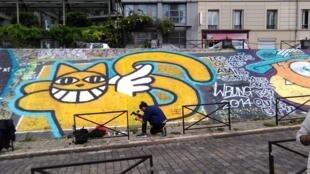 O grafiteiro franco-suíço Thoma Vuille, desenhando o célebre Monsieur Chat em um muro de Paris.