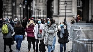 Tourists wearing a protective face mask amid fears of the spread of the COVID-19 novel coronavirus walk near the Pyramide du Louvre on 28 February, 2020 in Paris.