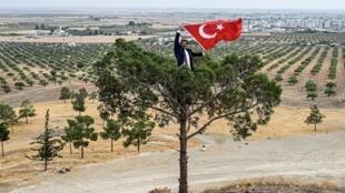 Un homme arbore le drapeau turc près de la frontière, face à la ville syrienne de Ras al-Aïn, le 19 octobre 2019.