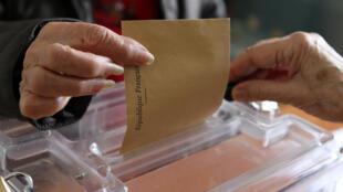 Eleitora francesa deposita voto na urna no primeiro turno das eleições departamentais, em 22 de março.