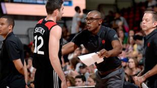 Patrick Mutombo (D) discute avec un joueur des Toronto Raptors, en juillet 2017 à Las Vegas.