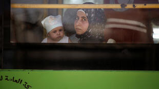 A woman and a child ride a bus, after reports of an agreement between rebels and Syria's army to evacuate civilians and rebel fighters from Mouadamiya, in Damascus, Syria September 2, 2016.