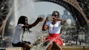 Tourists splash in a public fountain near the Eiffel Tower in Paris, 22 June 2019.