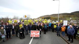 Les manifestants contre toute frontière entre l'Irlande et l'Irlande du Nord à cause du Brexit tiennent des pancartes à la frontière de Carrickcarnan entre Newry (Irlande du Nord) et Dundalk (République irlandaise) le 30 mars 2019.