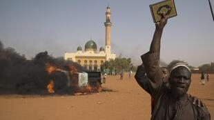 A man branishes a Koran in front of a burning car and a mosque in Niamey, 17 January 2015