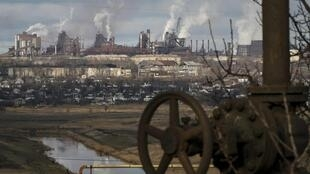 Au loin, de la fumée s'échappe des grandes cheminées des usines métallurgiques de la ville de Marioupol, dans l'est de l'Ukraine.