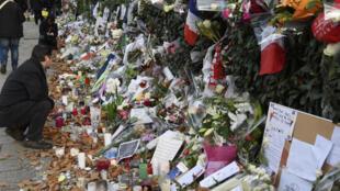 """Цветы и свечи в память о погибших в терактах в Париже 13 ноября 2015, перед концертным залом """"Батаклан"""""""