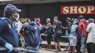 Des policiers sud-africains menacent des passants pour qu'ils respectent les règles de confinement devant un supermarché à Johannesbourg le 28 mars 2020.