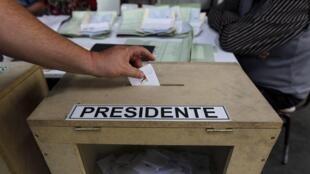 Un électeur glisse son bulletin de vote dans l'urne, à Santiago, au Chili, le 17 novembre 2013, lors du premier tour de l'élection présidentielle.