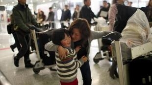 Hu Yi Xin embraces her daughter Rong Xi as she arrives from Egypt to the Pudon international in Shanghai