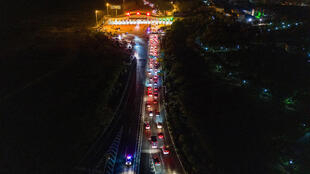 Cars queueing at a highway toll station in Wuhan in China's central Hubei province, as they prepare to leave the city after authorities lifted a more than two-month ban on outbound travel