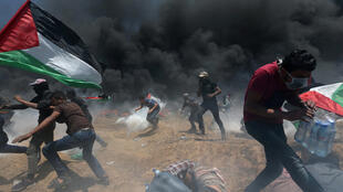 Palestinian demonstrators run for cover from Israeli fire and tear gas in Gaza on Monday