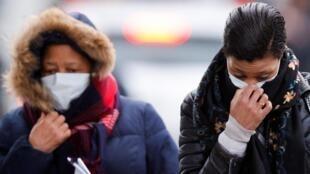 Des personnes portant des masques quittent l'hôpital de Creil, où des patients testés positifs au coronavirus ont été hospitalisés, le 27 février 2020.