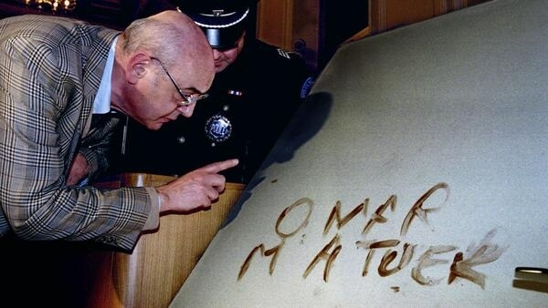"A file photo shows a man looking closely at the door with the message ""Omar m'a tuer"" (Omar killed me) in the courtroom in Nice, January 31, 1994."
