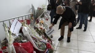 Turistas franceses depositam buquês de flores em homenagem às vítimas do atentado no Museu do Bardo, em Túnis.