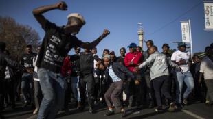 Des partisans de l'ancien président sud-africain Jacob Zuma acclament, dansent et chantent devant House Hill, lors de la comparution de l'ancien président sud-africain à la Commission Zondo à Johannesburg, le 15 juillet 2019.