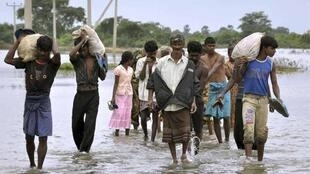 People cross a flooded road with supplies in Batticaloa district three days ago