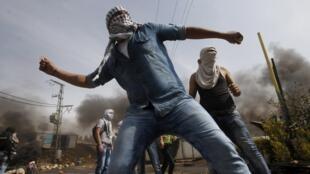 Palestinos lançam pedras contra tropas israelenses durante confrontos na cidade de Hebron, na Cisjordânia.