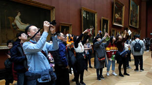 Visitors take pictures of paintings at the Louvre Museum in Paris, France, December 3, 2018. Picture taken December 3, 2018.