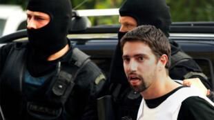 Greek policemen escort a suspect in Athens