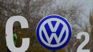 """Activista de Greenpeace con un cartel que reza """"CO2"""" usando el logo de la automotriz alemana frente a la sede de compañía en Wolfsburg, el 9 de noviembre de 2015."""