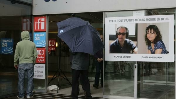 A poster with the portraits of reporter Ghislaine Dupont (R), 51, and radio technician Claude Verlon, 58, two French journalists killed in Mali at the entrance of the FMM building in Issy-les-Moulineaux near Paris in 2013.