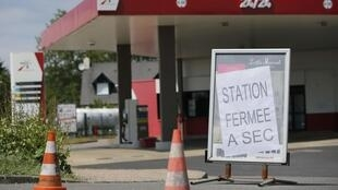 A placard which reads 'closed, dried up' is seen at a petrol station in Savenay, France