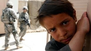 An Afghan boy and members of the U.S. 293 Military Police Company