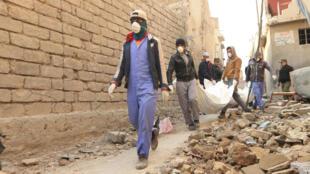 Des habitants de Mossoul qui déblayent les rues transportent des cadavres trouvés dans les décombres de la ville, le 17 janvier 2018.