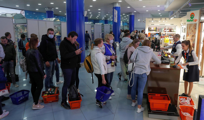 Люди в масках и без стоят в очереди в дьюти-фри минского аэропорта