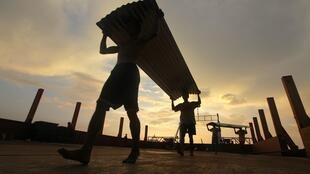 Workers carry construction material to be shipped to the area hit by Cyclone Girl