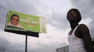 A man stands under a billboard of Haiti's presidential candidate Mirlande Manigat in Port-au-Prince