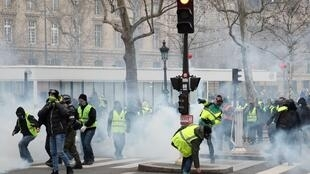 Protesters throw back police tear gas canisters in Paris, on the sidelines of a march in protest against police violence.