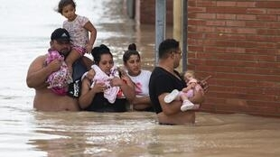 People wade through flood-waters in the south-eastern Spanish town of Almoradi.