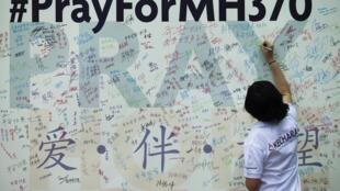 Mulher escreve mensagem para familiares de passageiros a bordo do avião desaparecido da Malaysia Airlines.