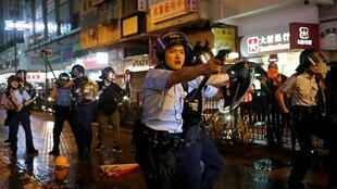 A policeman brandishes his gun at protesters in Hong Kong, 25 August 2019.