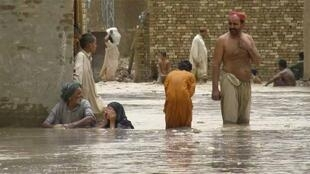 Residents wade through floodwaters in Bakhtiar Abad in Sibbi district