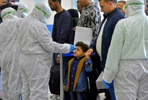 Un funcionario mide la temperatura corporal de un niño iraquí que regresa de Irán, en el aeropuerto internacional de Najaf el 21 de febrero de 2020