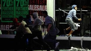 Looters run from a clothing store in Peckham, London