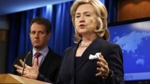 U.S. Treasury Secretary Geithner listens as Secretary of State Clinton speaks about Iran