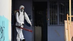 در سالونیک دومین شهر بزرگ یونان، یک مامور دولتی مدرسهای را ضدعفونی میکند
