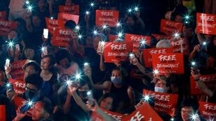 Demonstrators wave their smartphones during a rally ahead of the G20 summit, urging the international community to back their demands for the government to withdraw a the extradition bill in Hong Kong, China June 26, 2019.
