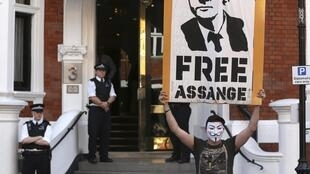 A protestor holds a poster of Wikileaks founder Julian Assange outside Ecuador's embassy in London